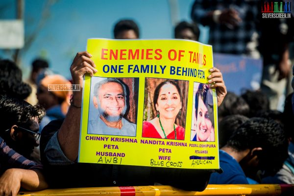 Protesters hold a banner against PETA at the Marina Beach